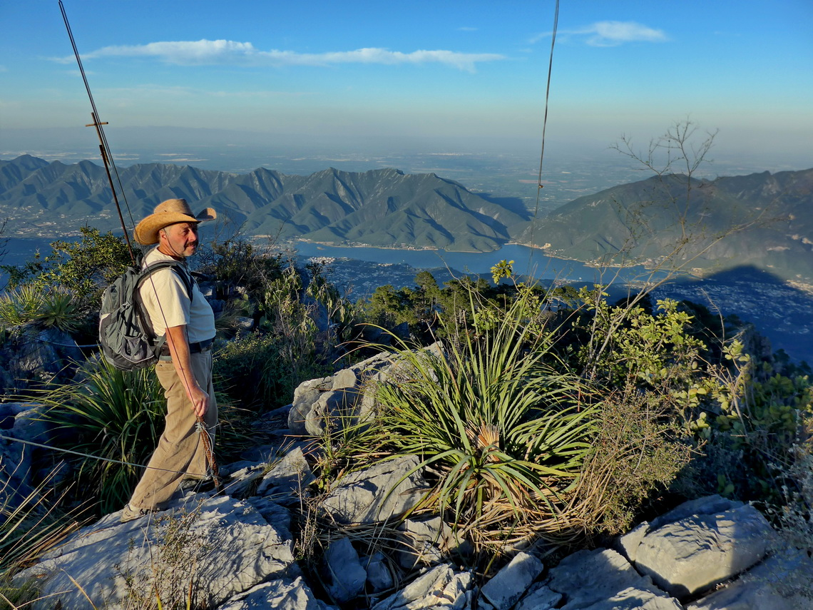 Tommy on the summit of 1847 meters high cerro Puerto Gringo with lake Presa Rodrigo Gomez