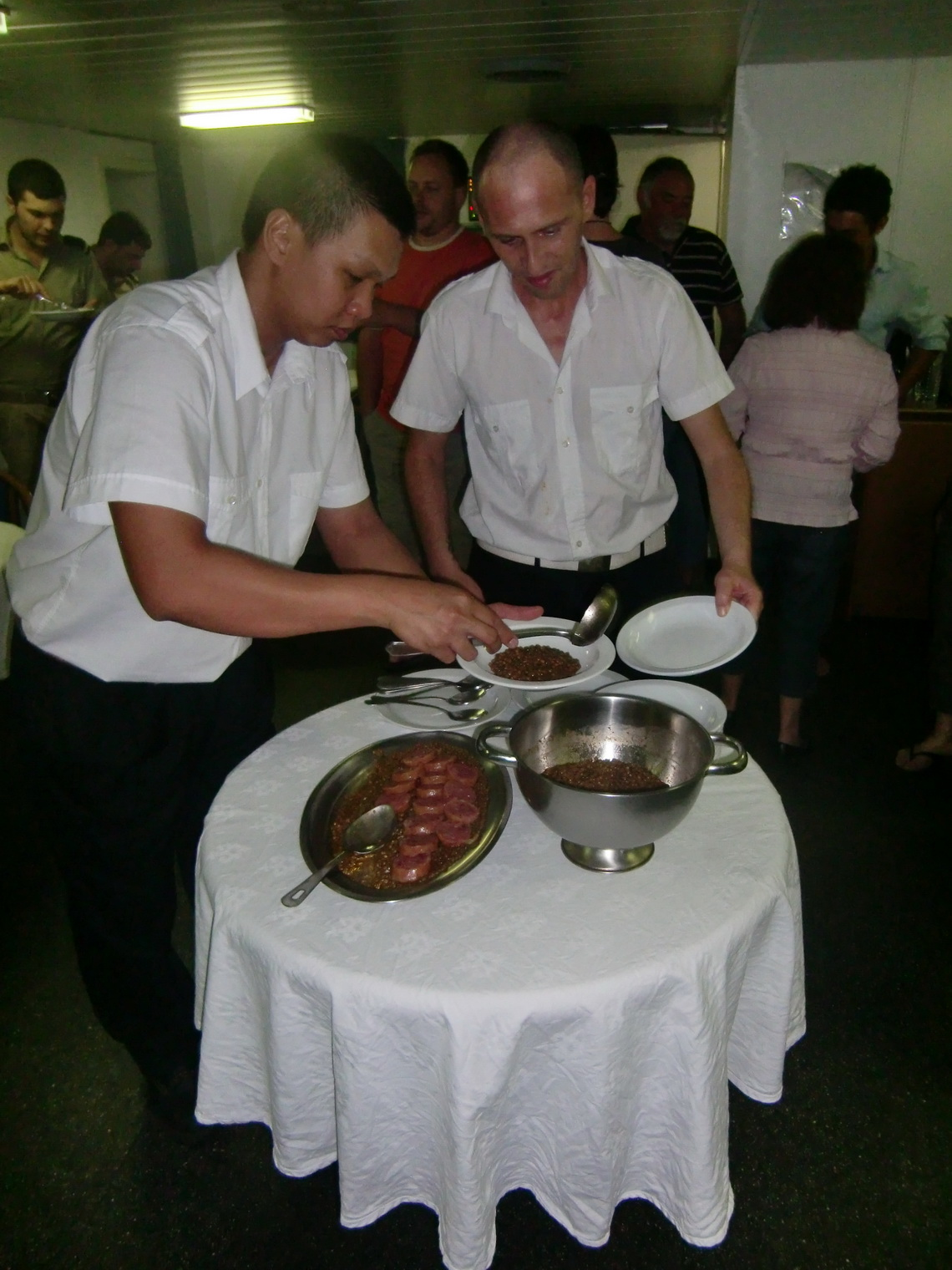 Rumen and Massimo serving lenses with sausages