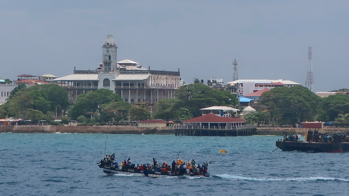 Crowded boat with Sultans Palace of Stone Town
