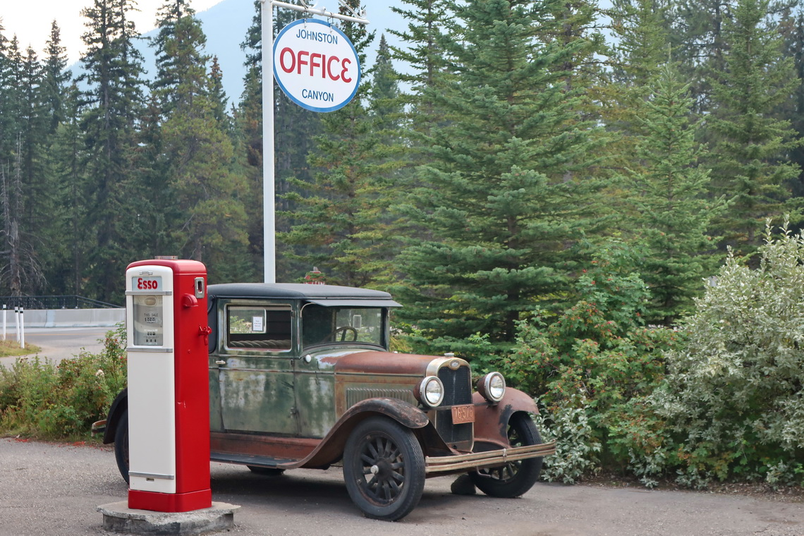 Oldtimer with ancient gas station on the parking lot of Johnston Canyon