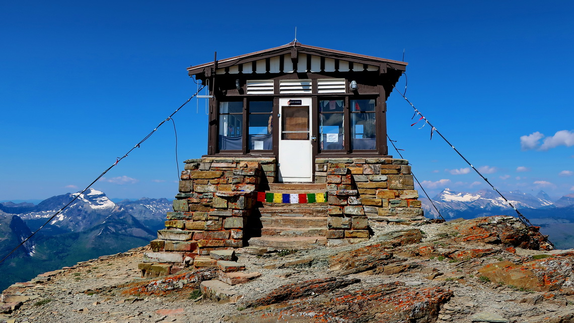 Fire vantage hut with Nepali flags on top of Swiftcurrent Peak