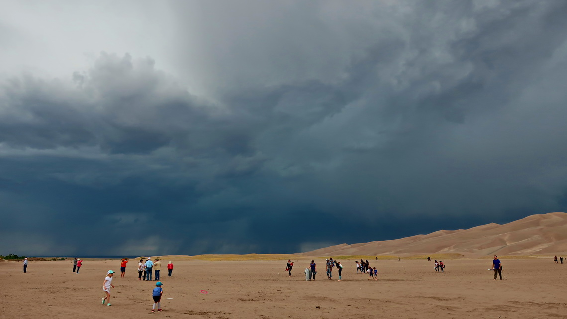 Crowded Great Sand Dunes with black clouds - thunder and lightning are coming!
