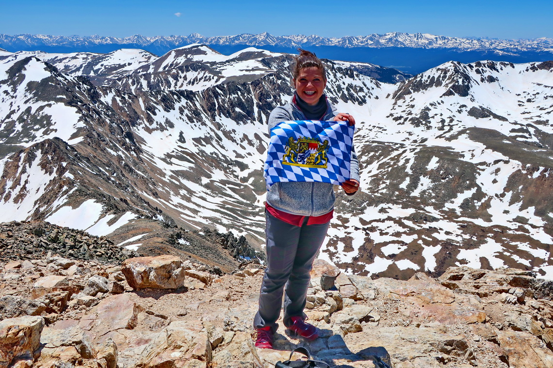 Girl from Colorado with Bavarian flag on Mount Democrat