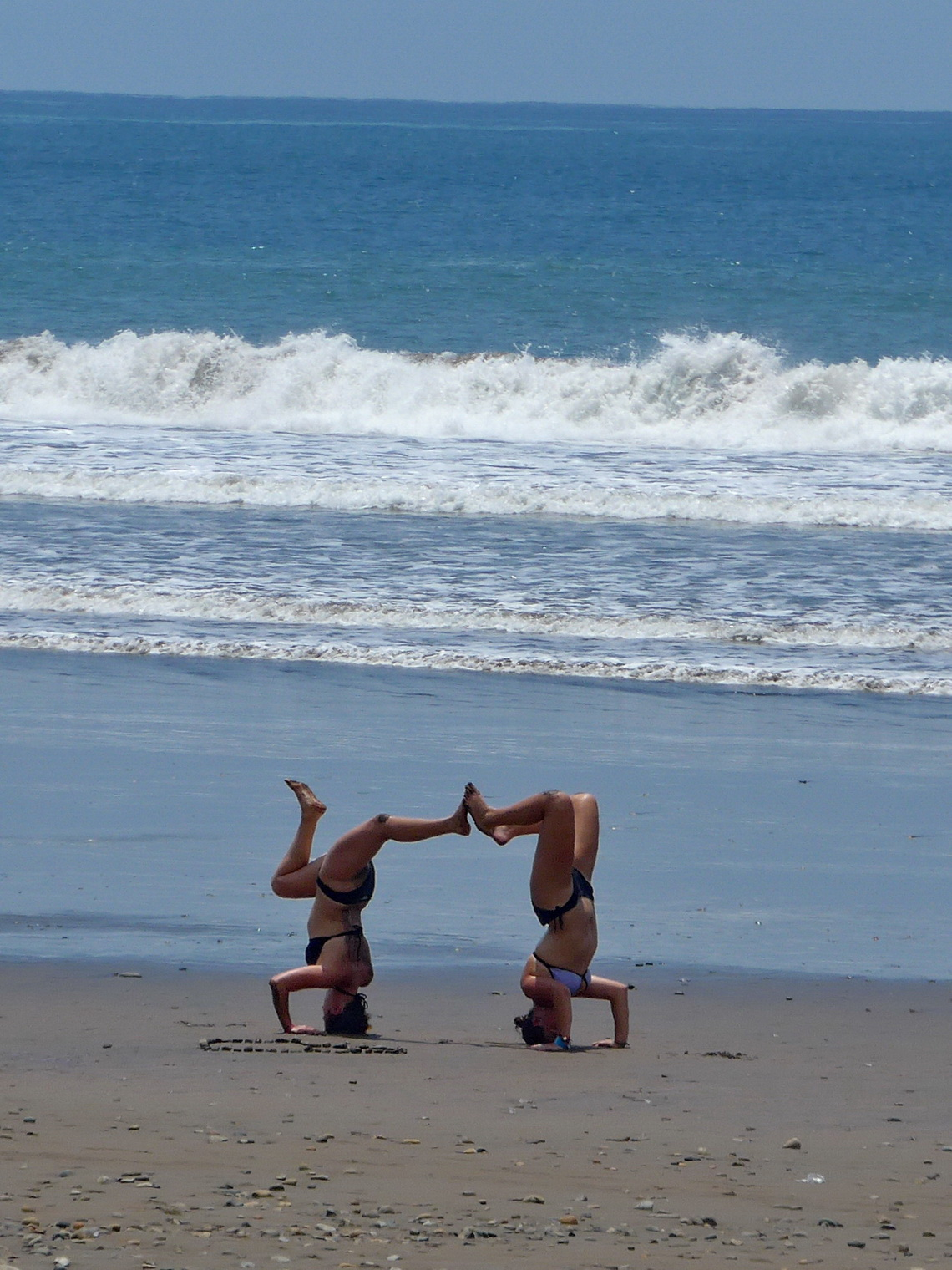 Two girls exercising in front of the Pacific Ocean