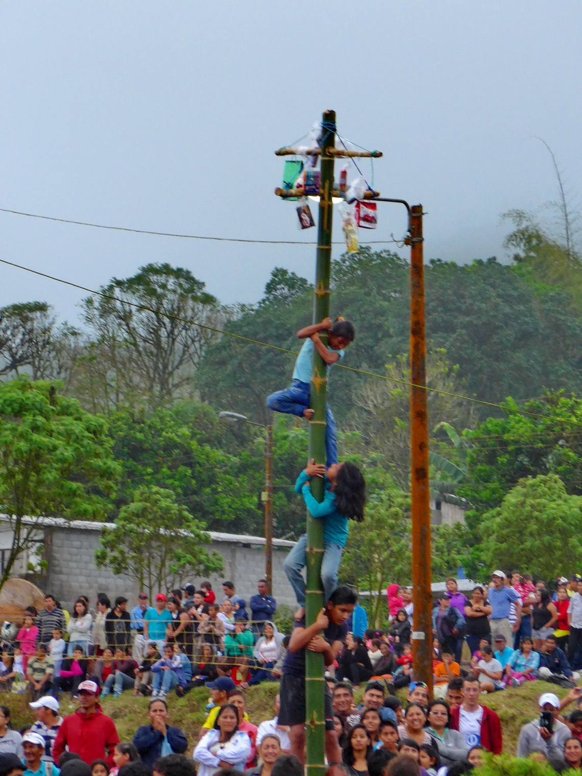 Fiesta in Santa Rosa - Kids trying to catch gifts on top of a slippery bamboo trunk