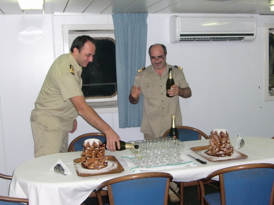 Captain and Director serving champagne